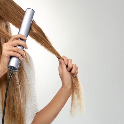 A woman flat ironing her hair
