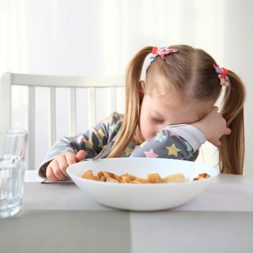 A small girl asleep at the breakfast table, a bowel of cereal is in front of her