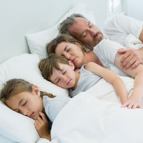 A father and mother are sleeping in a bed with their 2 children. All of the linens are white.ng in a bed
