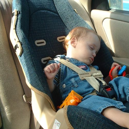 A baby boy asleep in a car seat