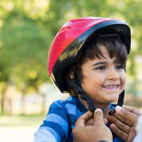 A young boy with a red bicycle helmet.