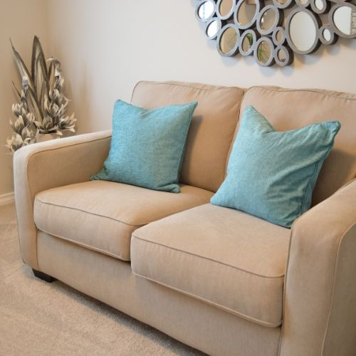 A tan couch with two baby blue pillows