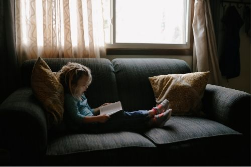 A girl with head lice sitting on a couch reading a book