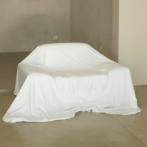 A couch covered in a clean white sheet