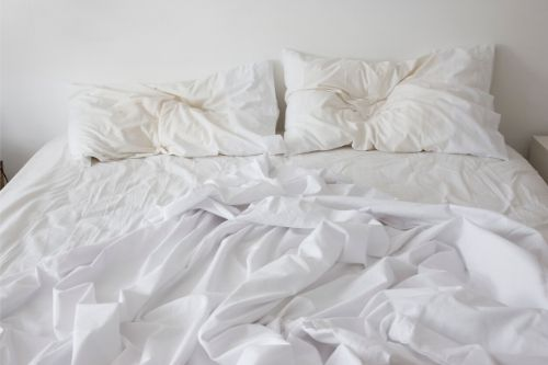 A messy bed with two pillows.