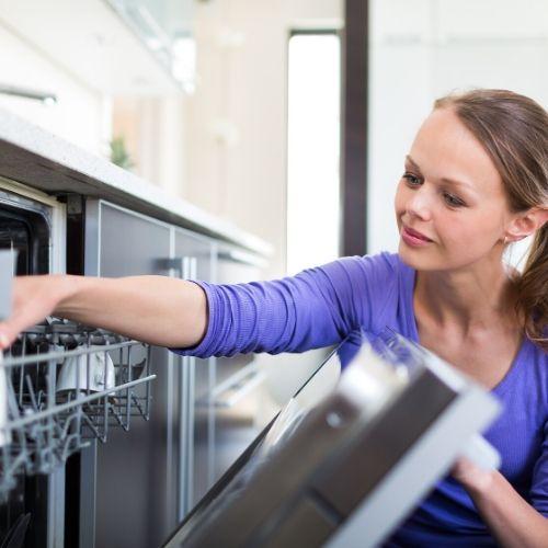 Una mujer cargando un lavavajillas.