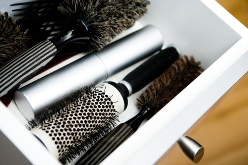 A drawer with several hair brushes in it.