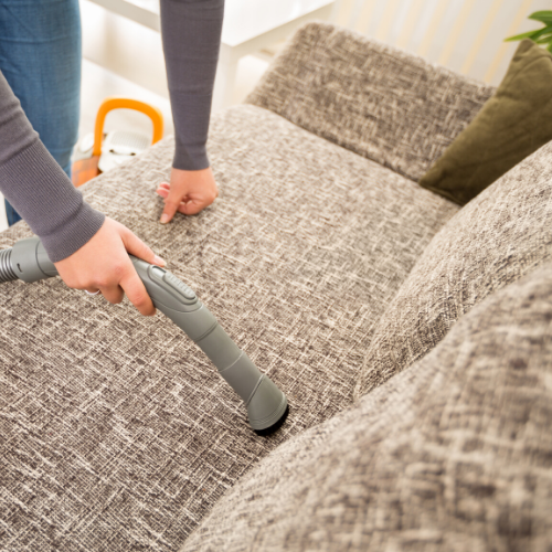 A woman vacuuming her couch